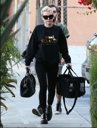 Miley Cyrus w czarnej bluzie ze złotym nadrukiem (źródło: pinterest.com)