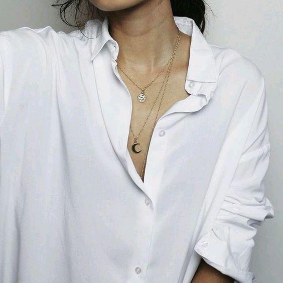 prosta biała koszula, której wykończeniem jest delikatna złota biżuteria