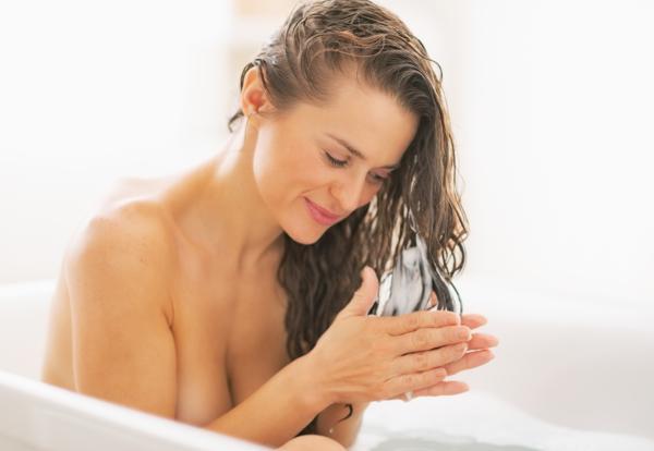 pielęgnacja włosów wykonywana przez młodą kobietę siedząc w wannie