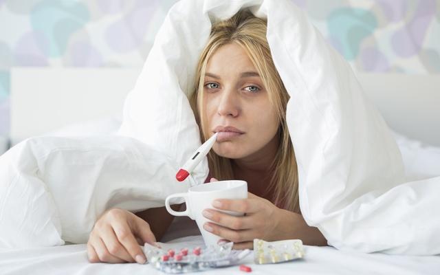 chora kobieta na naciągniętą kołdrę na głowę i trzyma termomert w ustach i ma objawy grypy