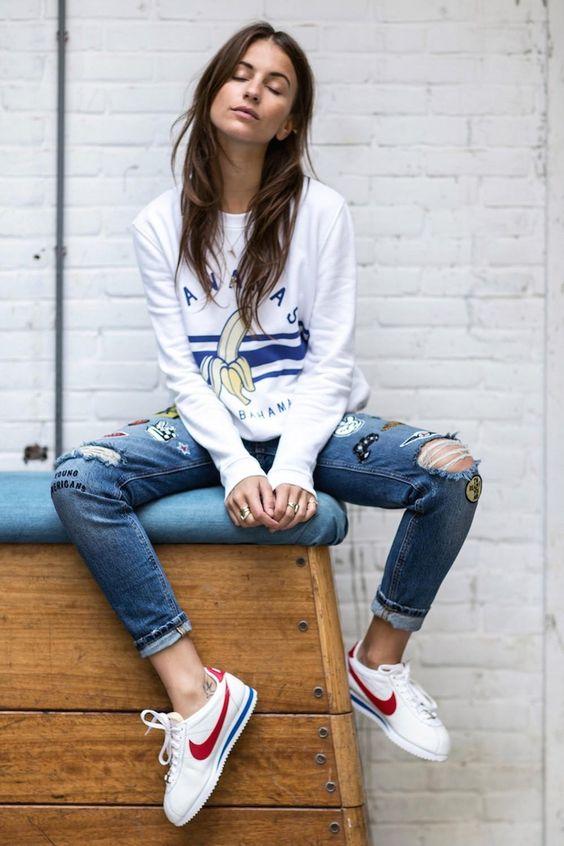 jeansy z dziurami i kolorowymi naszywkami w połączeniu z bluzą z modnym printem, do tego sportowe obuwie