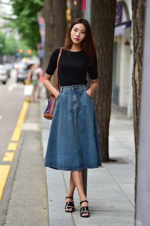 młoda dziewczyna w jeansowej za kolano spódnicy w kształcie litery A do czarnej prostej bawełnianej bluzki i czarnych sandałków na płaskim obcasie