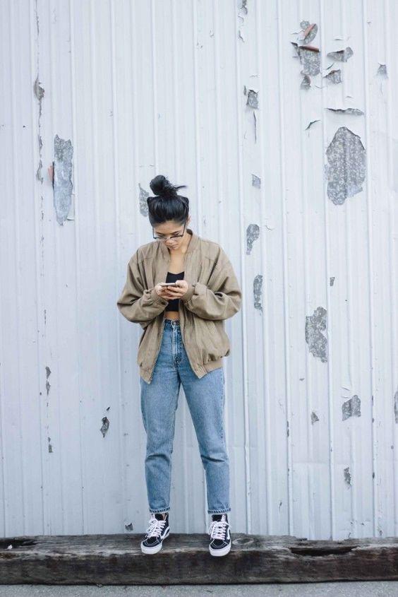młoda dziewczyna w mom jeans i beżowej bomberce