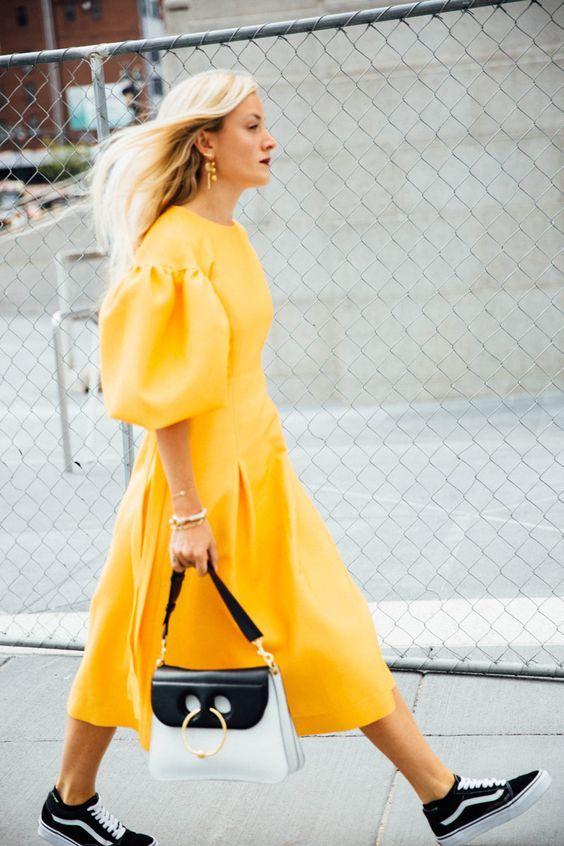 modelka w intensywnie żółtej sukience do połowy łydki i bufiastymi rękawami połączonej z czarno-białymi dodatkami w formia sportowego obuwia i torebli