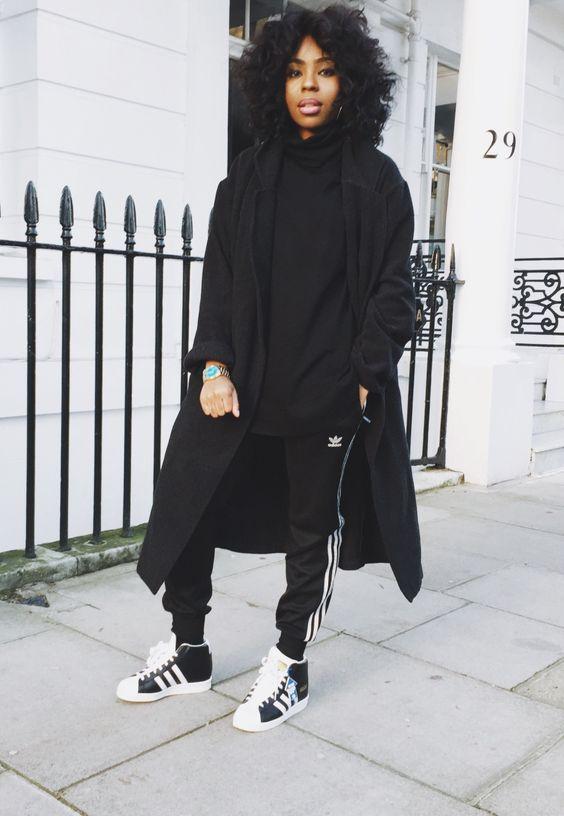 afro-amerykanka w czarnych spodniach dresowych adidas połączonych z pudełkowym czarnym płaszczem i butami sportowymi na obcasie