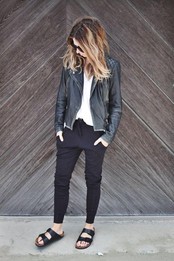 modelka w ciemnych spodniach dresowych połączonych z klapkami i czarną ramoneską
