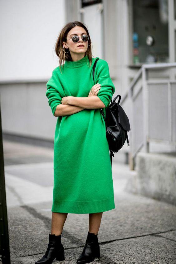 modelka w dzianinowej sukience z długimi rękawami w modnym kolorze mocnej zieleni i pasującymi czarnymi sztybletami i skórzanym plecakiem zarzuconym na jedno ramię