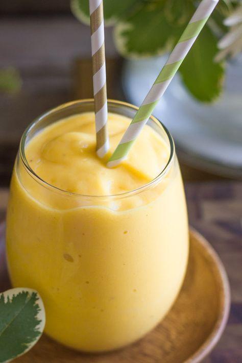smoothie mango ananas podany w pękatej szklance z dwiema słomkami w paski biało zielone i biało złote
