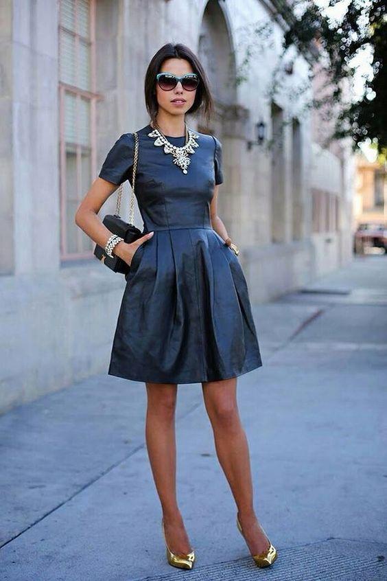 modelka w krótkiej przed kolano czarnej skórzanej sukience z bufiastą częścią spódnicy założoną do złotych szpilek