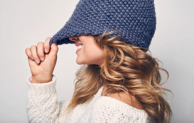 młoda dziewczyna z pięknymi włosami naciąga z uśmiechem granatową czapkę na oczy